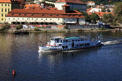 The boat floating on the Vltava River, historic buildings, Prague, Czech Republic Stock Image