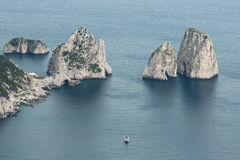 Boat floating on water, Capri. Sea view from hill in Capri. Boat floating next to rock formations Stock Photos