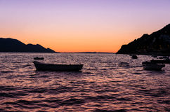 Boat floating on water at sunset Royalty Free Stock Photo