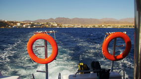 Boat is Floating on the Waves and Leaves a Trail in the Red Sea. Red life buoys on the stern of the ship. Lifebuoy on the yacht in the sea. Shot of a water stock video footage