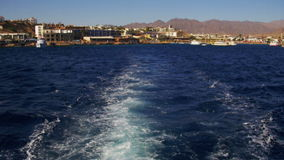 Boat is Floating on the Waves and Leaves a Trail in the Red Sea. Red life buoys on the stern of the ship. Lifebuoy on the yacht in the sea. Shot of a water stock footage