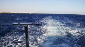 Boat is Floating on the Waves and Leaves a Trail in the Red Sea. View from stern of the ship. Yacht in the sea. Shot of a water wake of a tour boat leaving stock video