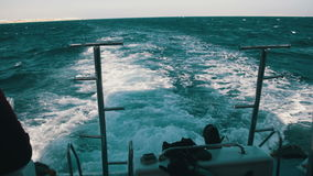 Boat is Floating on the Waves and Leaves a Trail in the Red Sea. View from stern of the ship. Yacht in the sea. Shot of a water wake of a tour boat leaving stock video footage