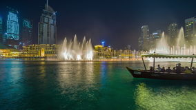 The boat floats against the background of a dancing fountain in Dubai. 4K Timelapse in Dubai, United Arab Emirates stock video