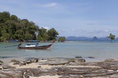 The boat floats on the background of the beautiful island.Traditional Thai Fishing boats with colorful ribbons and flags. Thailand Royalty Free Stock Photos