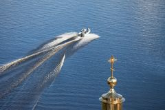 The boat floats on the lake in summer. Golden dome and cross. stock photo