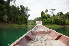 The boat floats on the lake . Thai wooden boat floats on quiet tropical lake royalty free stock photography
