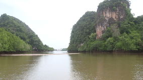 Boat Floats on the River of Mangroves. Boat floats on the river with muddy water of the mangroves on the background of two rocks covered with greens stock video footage