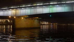 Boat floats the river under bridge in night. Camera inside boat. stock footage