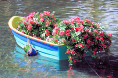 Boat with flowers. Boat floating along the water with flowers Stock Photo