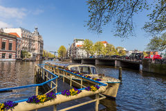 Boat with flowers on the canal near bridge in Amsterdam Royalty Free Stock Photo