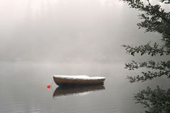 Boat on Foggy Lake. A row boat anchored on the calm lake in the foggy autumn stock photos