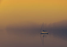 Boat on foggy lake windermere Stock Photos