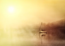 Boat on foggy lake windermere Stock Image