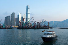 Boat and freighter in Victoria Harbour, Hong Kong Stock Photography