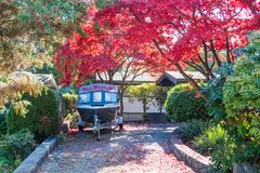 Boat in front of the autumn trees on a backyard. Small motor boat on a trailer staying on a backyard under a colored autumn trees in sunny weather Royalty Free Stock Photos