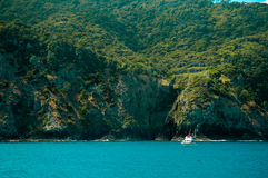Boat in front of a green island royalty free stock image