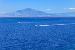 Boat in front of Mount Vesuvius in Bay of Naples at Sorrento. Resort town royalty free stock photos