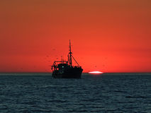 Boat in front of a sunset at the horizon Stock Photography