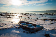 Boat frozen in fjord in winter sunshine Stock Images