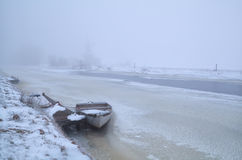 Boat on frozen river in foggy winter day Stock Photo