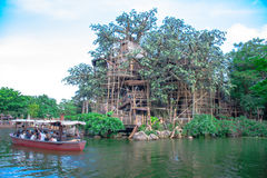 A boat full of passengers travelling through the river around the Tarzan Tree House in Hong Kong Royalty Free Stock Image