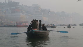 Boat full of people sailing down the Ganges, with other boats in background. stock video