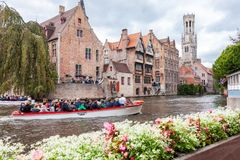 Boat full of tourists in the water canal of Bruges in Belgium Stock Photo