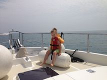 On the boat. Girl sitting on the boat in the life vest stock images