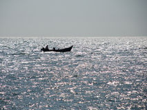 Boat and Glittering Sea. Fishermen are returning in the afternoon Stock Photo