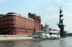 The boat goes past the factory Red October on the Moscow river. Stock Photos