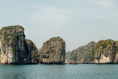 Boat goes between Scenic mountain rock face cliff in the sea water, green trees, asia ha long bay vietnam stock image