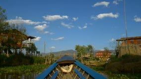 Boat going through floating village, Inle Lake, Myanmar stock video