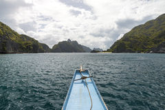 Boat going between green islands with dramatic clouds Stock Photography