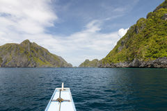 Boat going between green islands Royalty Free Stock Photography