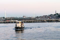Boat and Golden Horn Metro Bridge in Istanbul. Travel to Turkey - excursion boat and view of Golden Horn Metro Bridge in Istanbul city in spring evening stock images