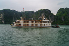 Boat in Halong Bay. Tourist ship in Halong Bay and a small fishing boat Royalty Free Stock Images