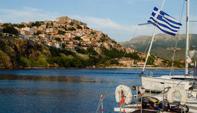 Boat in the harbor with castle on the hill at Molyvos Greece. Twilight at the seaside town of Molyvos on the island of Lesvos in Greece royalty free stock images