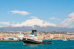 Boat at the harbor of Catania. A tug boat leaving the harbor of Catania. Volcano Etna in the background stock photography