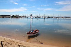 Boat in Harbour. A little boat lies on the edge of the boat harbour its lone mast upright with its sails in the bottom of the boat stock image