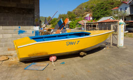 A boat hauled out for painting at a fishing village in the caribbean. A hand-made wooden vessel used for fishing as seen on bequia in the windward islands royalty free stock image