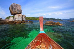 Boat heading to large stack stone arch. Boat on crystal sea heading to large stack stone arch near Koh Lipe, Thailand Stock Photography