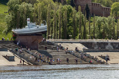 Boat Hero at the foot of Chkalov Stairs in Nizhny Novgorod. Nizhny Novgorod. People resting on the Nizhne-Volzhskaya Embankment in a sunny weekend Stock Photo