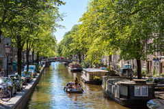 A boat on the historic canals center of Amsterdam. A smal boat with girls on the historic Egelantiers gracht in the center of the Dutch city Amsterdam stock images