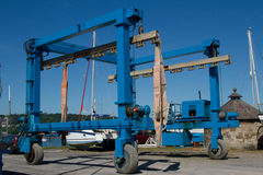 Boat hoist. Blue painted boat hoist on wheels with hydrolic hoses and canvas support strapping Royalty Free Stock Image