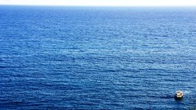 Boat on the horizon. Smal tourist boat caught on the open sea royalty free stock photography