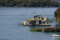 Boat House. Some house boats on a lake. One of the houses uses a fishing net royalty free stock images