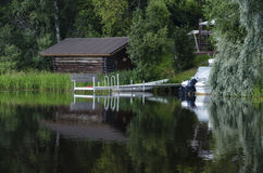 Boat house and boat reflecting on lake Royalty Free Stock Photos