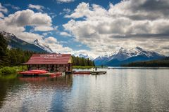 Boat house and canoes on a jetty at Maligne Lake in Jasper National Park. Canada, with snow-covered peaks of canadian Rocky Mountains in the background Stock Photography