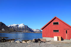 Boat house, church and snowy mounts Stock Photos